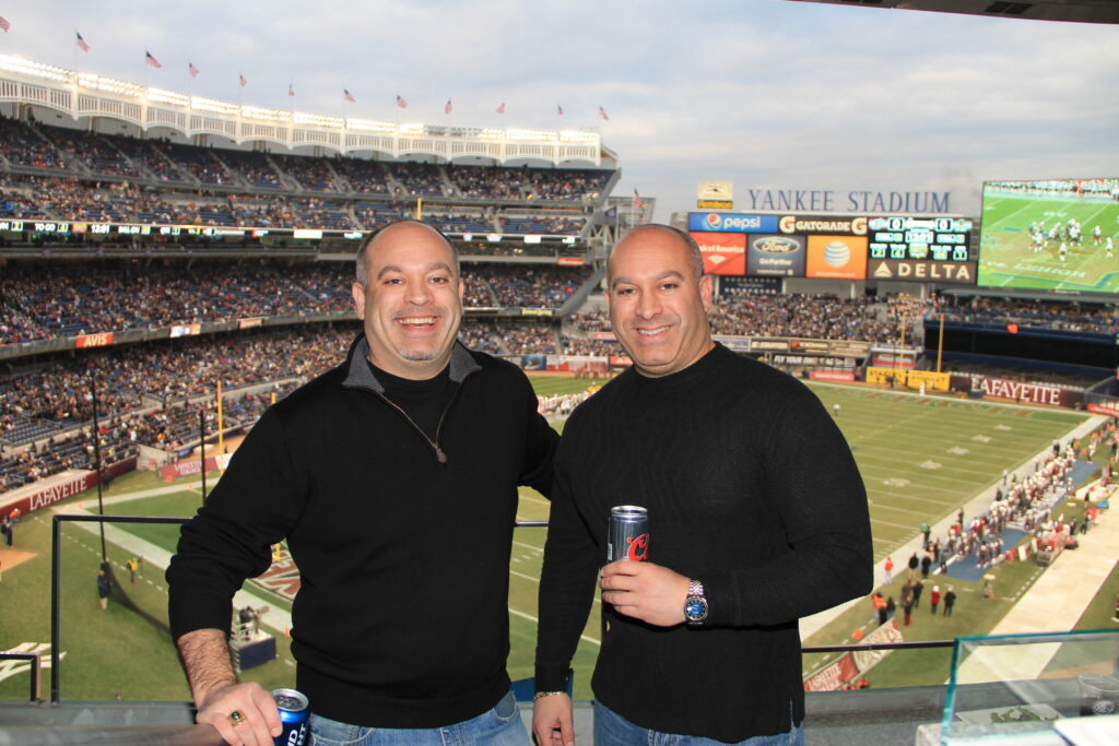 Mike Watkins standing in a stadium with his twin brother